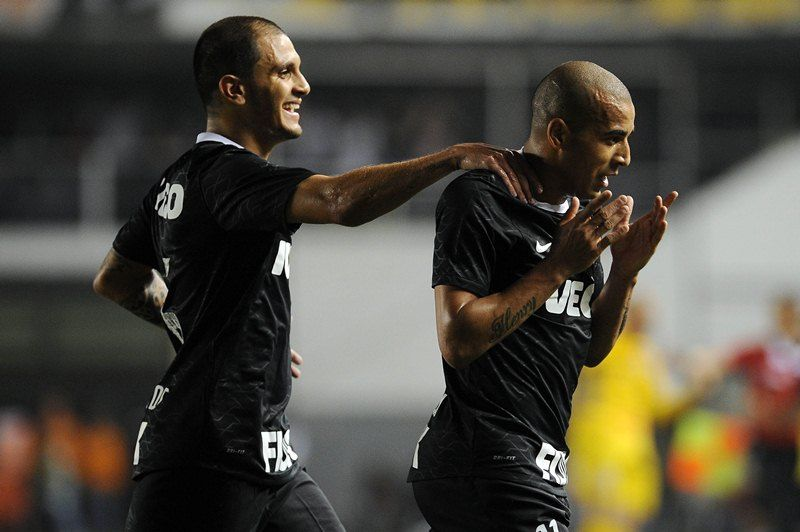 Emerson (R) of Brazil?s Corinthians, celebrates his goal scored against Brazil?s Santos FC with teammate Fabio Santos (L), during their 2012 Copa Libertadores semifinal 1st leg football match held at Vila Belmiro stadium, in Santos, some 60 km south of Sao Paulo, Brazil, on June 13, 2012. AFP PHOTO / Nelson ALMEIDA