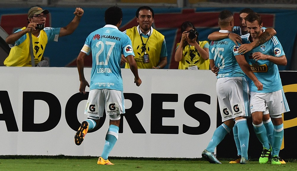 Perus Sporting Cristal player Gabriel Costa (3-R) and teammates celebrate after scoring a goal against Argentinas Huracan during their  Copa Libertadores football match at the National Stadium in Lima, Peru on March 8, 2016. AFP PHOTO/CRIS BOURONCLE / AFP / CRIS BOURONCLE        (Photo credit should read CRIS BOURONCLE/AFP/Getty Images)
