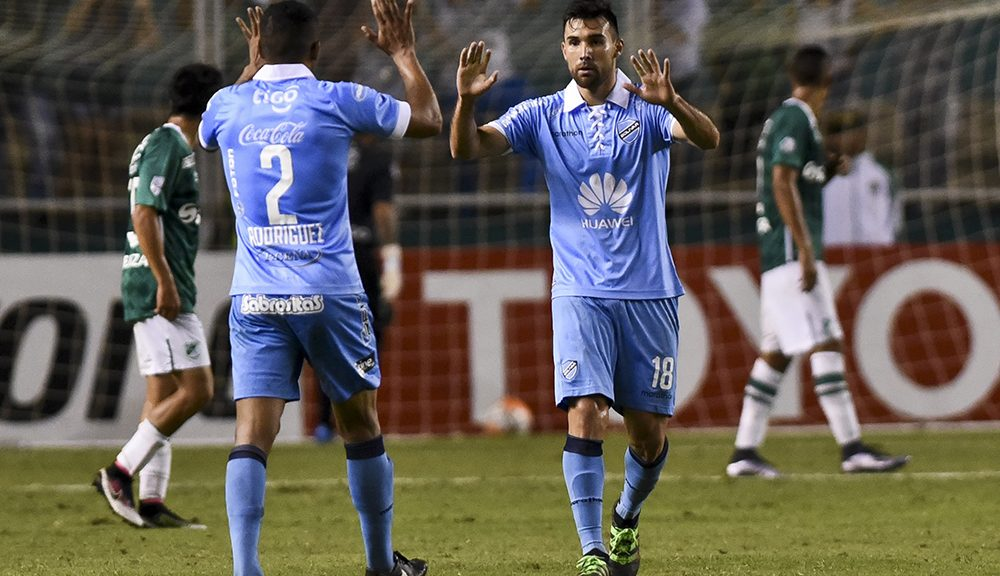 Bolivia's Bolivar defender Edemir Rodriguez (L) and midfielder Danny Bejarano celebrate their goal scores by defender Argentinian Gaston Cellerino (Out to frame) against Colombian Deportivo Cali during their Copa Libertadores 2016 tournament football match at Deportivo Cali stadium, in Palmira, Colombia, on April 14, 2016. / AFP / LUIS ROBAYO        (Photo credit should read LUIS ROBAYO/AFP/Getty Images)