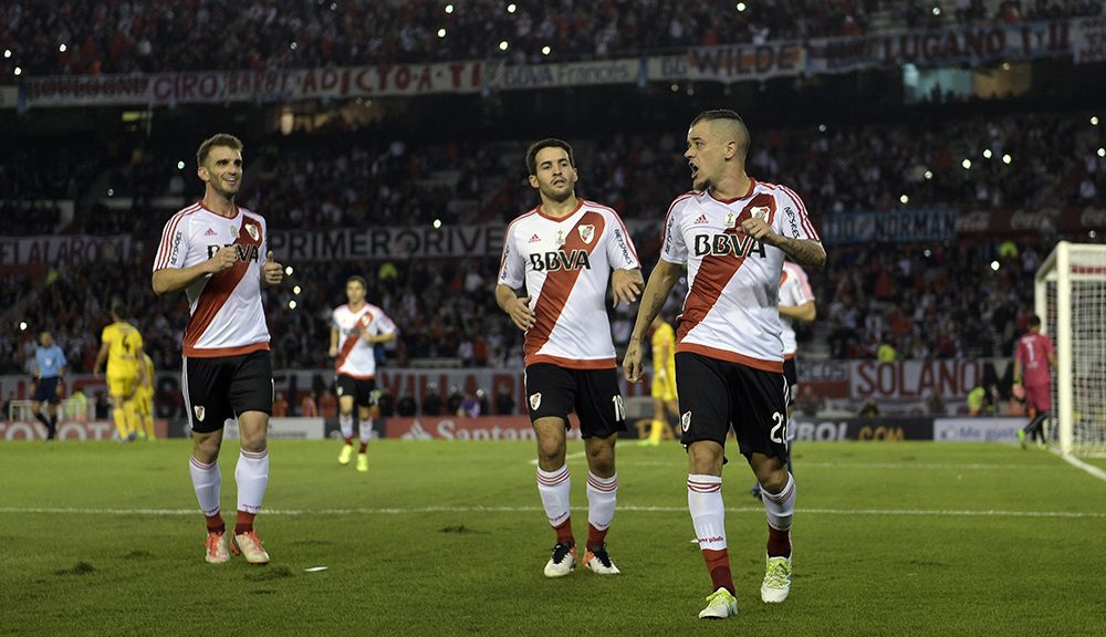 Argentina's River Plate midfielder Andres D'Alessandro (R) celebrates after scoring a penalty the team's second goal with teammates midfielder Camilo Mayada (C) and forward Ivan Alonzo during the Copa Libertadores 2016 group 1 football match against Venezuela's Trujillanos at the Monumental stadium, Buenos Aires, Argentina, on April 21, 2016. River Plate won 4-3. / AFP / JUAN MABROMATA        (Photo credit should read JUAN MABROMATA/AFP/Getty Images)