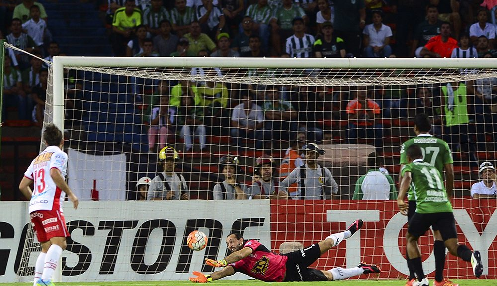 Goalkeeper Marcos Diaz (C) of Argentina's team Huracan pulls off a save during the Libertadores Cup Group 4 football match against Colombia's Atletico Nacional at the Atanasio Girardot stadium in Medellin, Antioquia department, Colombia, on April 19, 2016. / AFP / RAUL ARBOLEDA        (Photo credit should read RAUL ARBOLEDA/AFP/Getty Images)